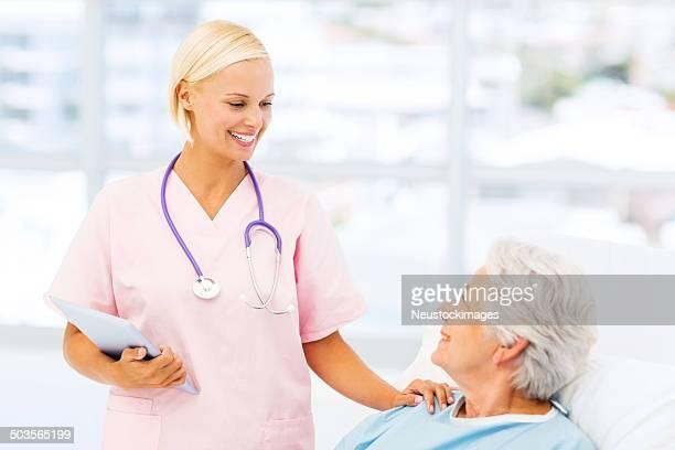 笑顔の看護師慰める女性の患者の病院へ