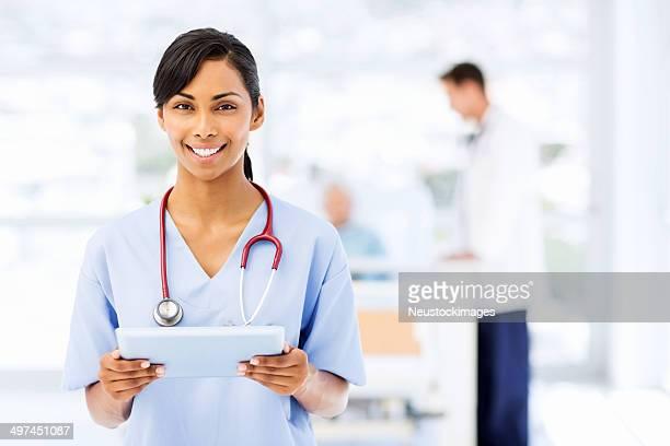 Lächelnd Krankenschwester Holding Tablet PC im Krankenhaus
