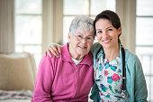 Smiling nurse hugging patient in home