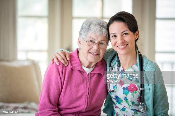 Smiling nurse hugging patient in home