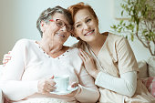 Smiling nurse in beige uniform hugs old lady drinking tea while sitting on white sofa in nursing home