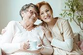 Smiling nurse in beige uniform hugs old lady drinking tea while sitting on white sofa in nursing home