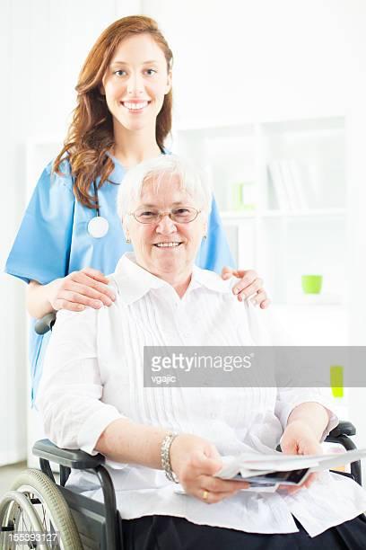 Souriant Infirmière en prenant soin d'une femme Senior en fauteuil roulant.