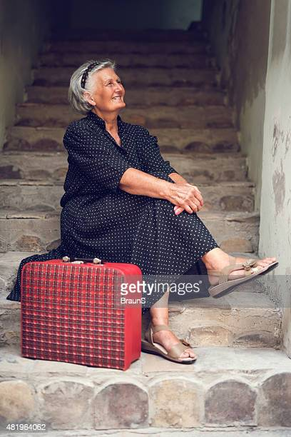 Smiling old woman relaxing on stairs with a suitcase.