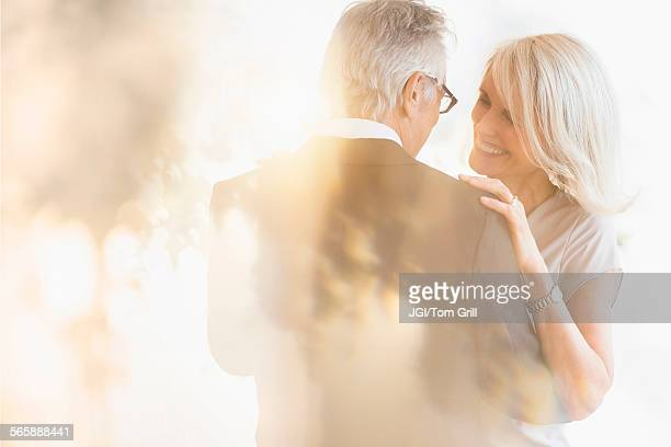 Smiling older Caucasian couple dancing