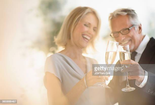 Smiling older Caucasian couple toasting with champagne