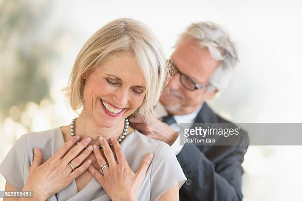 Smiling older Caucasian man giving wife a necklace