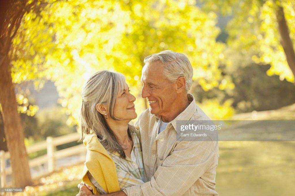 Smiling older couple hugging outdoors : Stock Photo