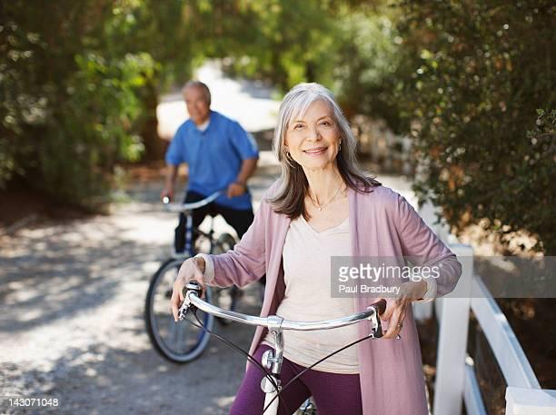 Souriant couple de retraités équitation vélos