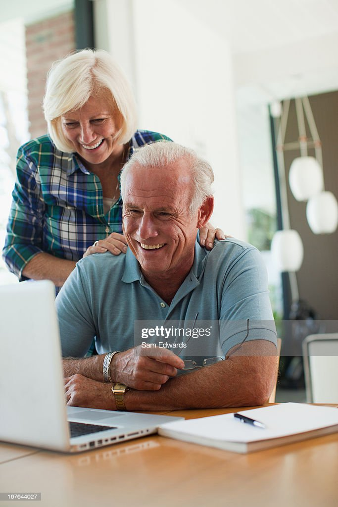 Smiling older couple using laptop together : Stock Photo