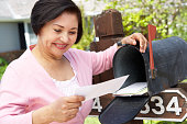 Senior Hispanic Woman Checking Mailbox Smiling