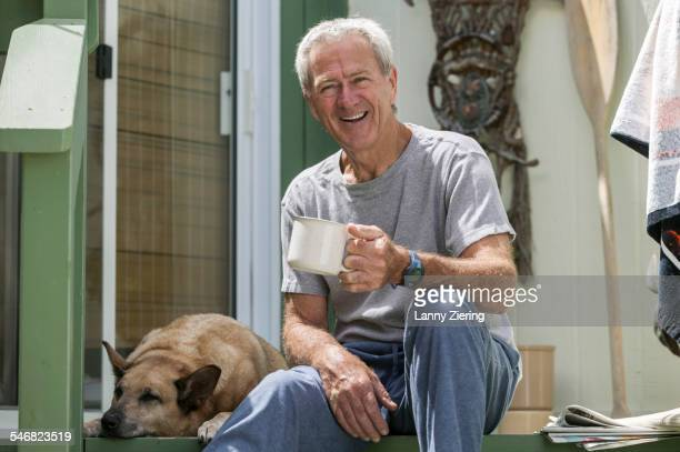 Smiling older man drinking coffee with dog on porch