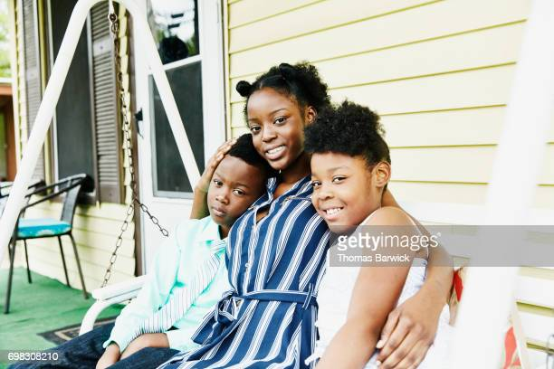 Smiling older sister sitting between siblings on swing on front porch of home