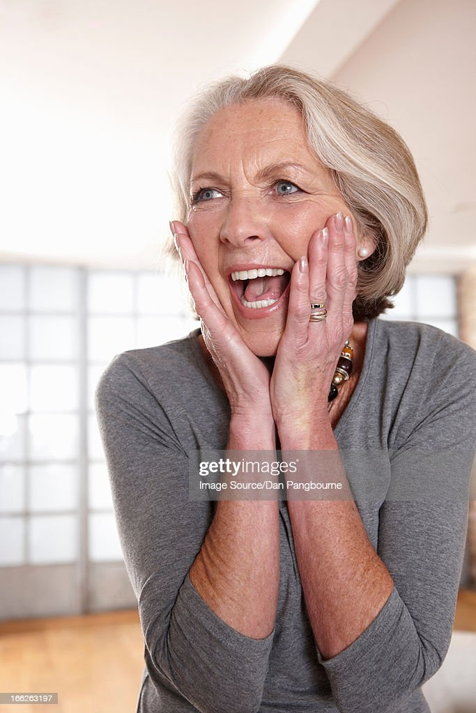 Smiling older woman gasping : Stock Photo