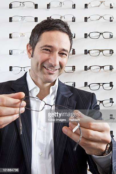 A smiling optician holding up a pair of glasses to the camera in an eyewear store