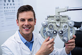 Smiling optometrist adjusting phoropter in ophthalmology clinic