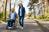 Breathing fresh air. Happy disabled male person sitting on his wheelchair looking forward while holding hands with his girlfriend