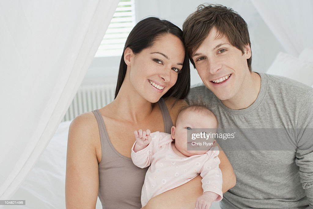 Smiling parents holding baby : Stock Photo