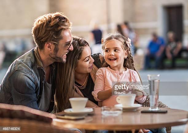 Lächelnd Eltern sprechen Ihre kleine Tochter in einem Café.