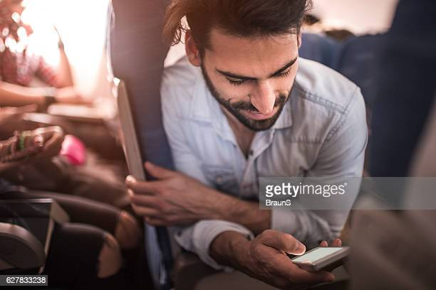 Smiling passenger reading a text message on smart phone.