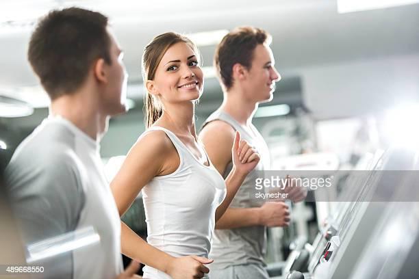 Souriant personnes faisant de l'exercice sur tapis de course dans la salle de sport.