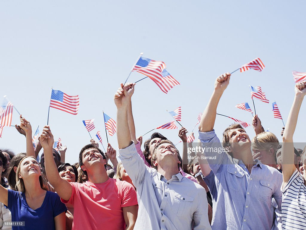 Smiling people waving American flags and looking up in crowd : Stock Photo