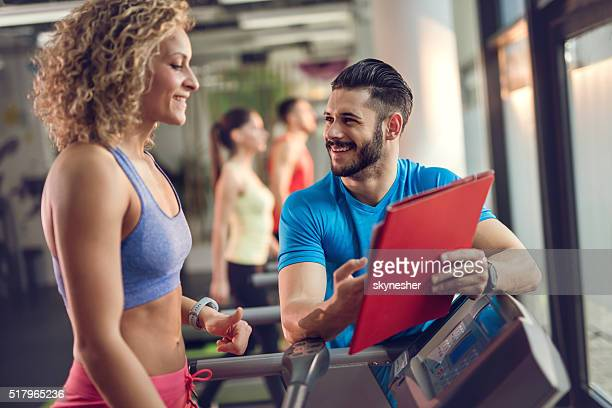 Smiling personal trainer assisting young woman in gym.