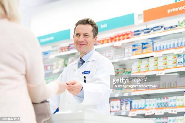 Smiling pharmacist assisting customer in pharmacy