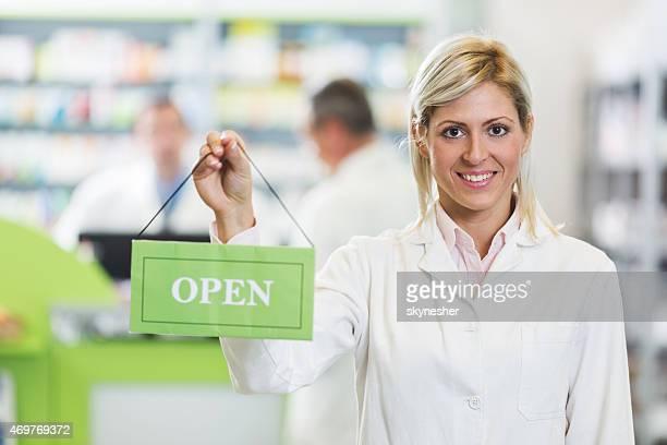 Smiling pharmacist holding open sign in pharmacy.