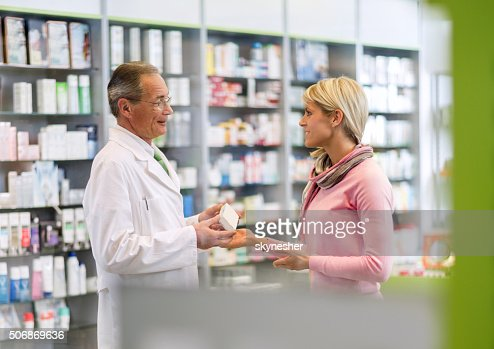 Smiling pharmacist talking young woman in a pharmacy.