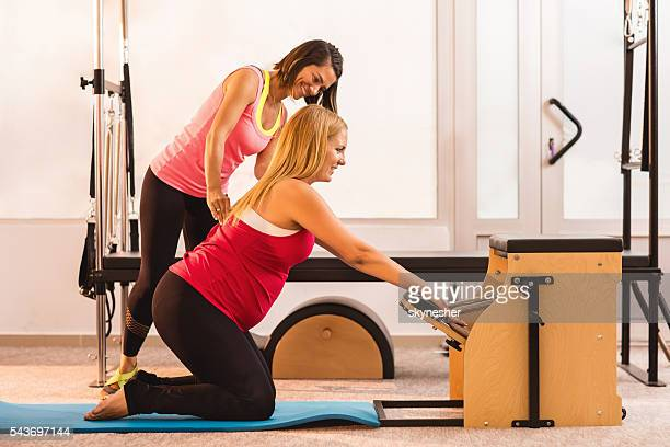 Smiling Pilates instructor assisting to pregnant woman during exercising.