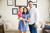 Smiling pregnant woman carrying son while standing by man in living room at home
