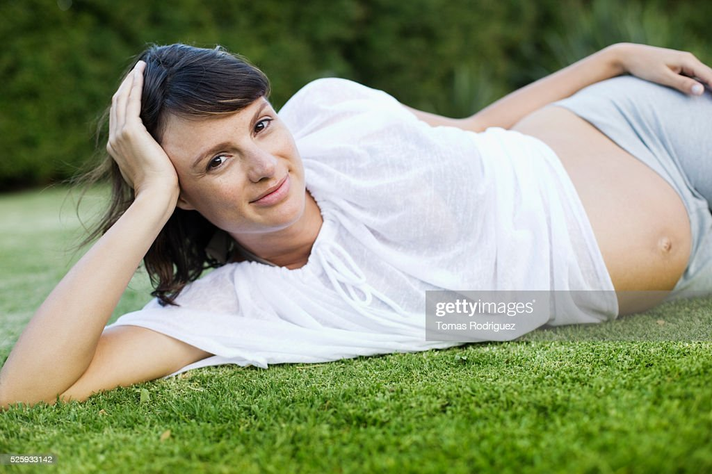 Smiling pregnant woman lying on grass : Foto de stock