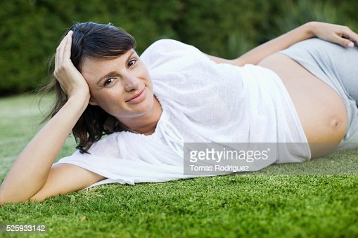 Smiling pregnant woman lying on grass : Stock Photo