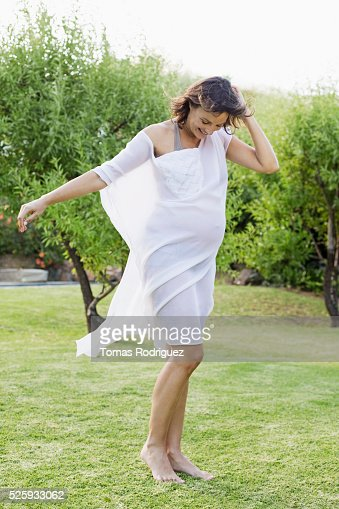 Smiling pregnant woman standing on grass : Foto de stock