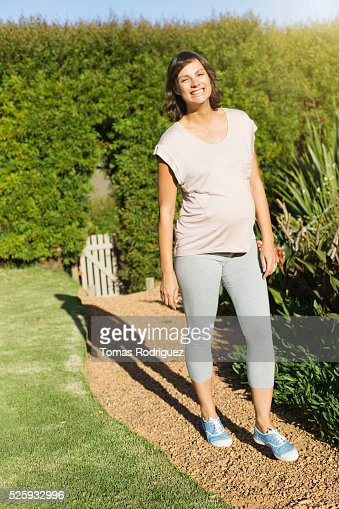 Smiling pregnant woman standing on path in garden : Stockfoto