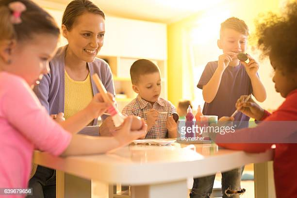 Smiling preschool teacher and children coloring Easter eggs together.
