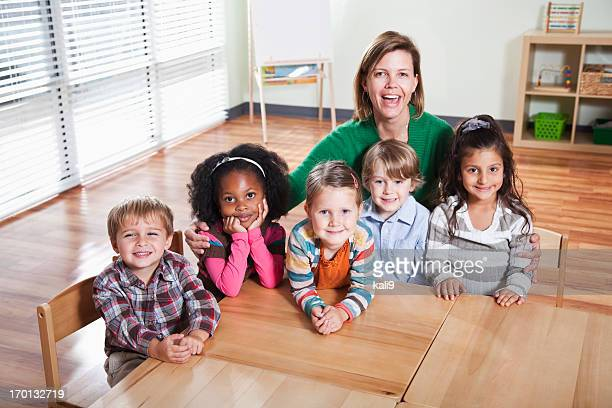 Smiling preschoolers and teacher sitting at table