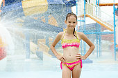 Smiling preteen girl standing under water drops. Blurred waterpark in background. Travel, fun, vacation concept. Text space