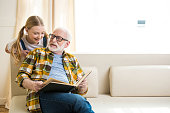 Smiling preteen girl with senior man in eyeglasses reading book together