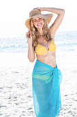 Smiling pretty blonde in bikini looking at camera at the beach