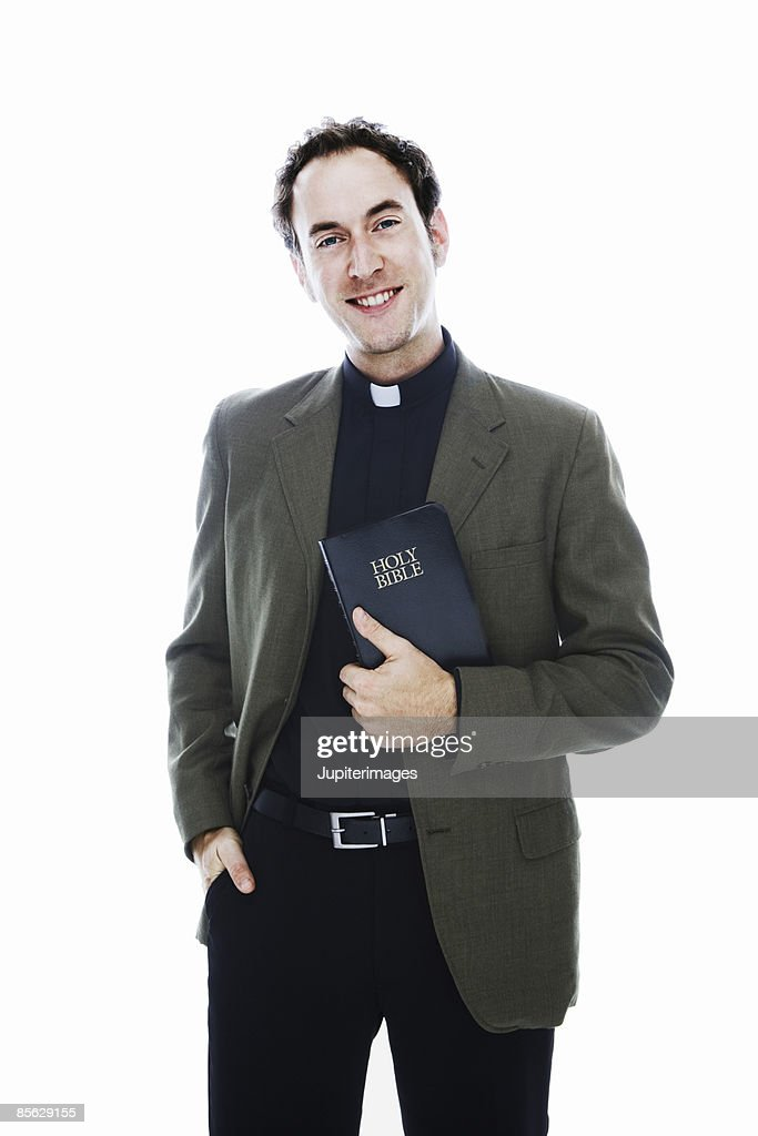 Smiling priest holding bible