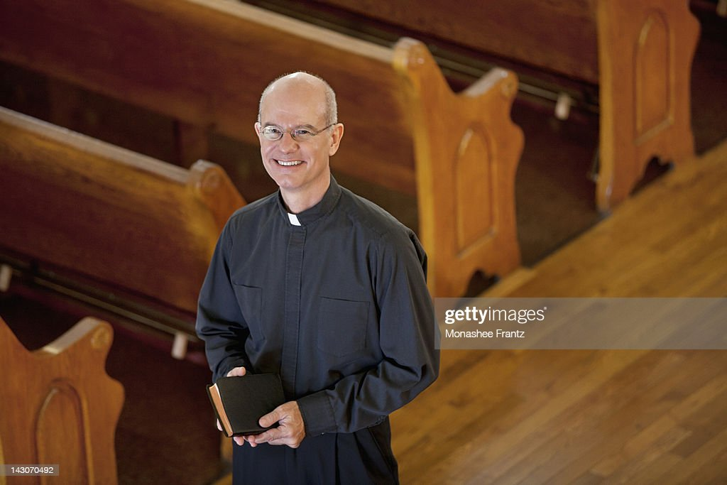 Smiling priest standing in church : Stock Photo