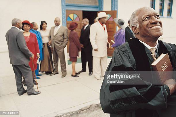 Smiling Priest Standing in Front of a Group of People Outside a Church Holding a Bible