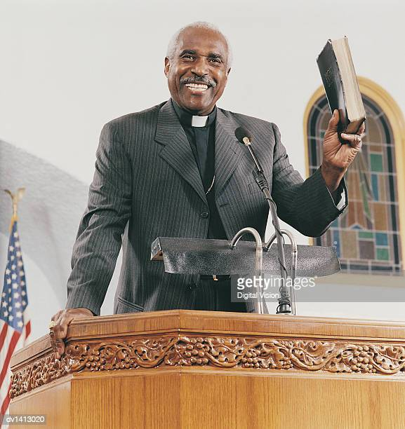 Smiling Priest Standing on a Pulpit at a Church Service and Holding a Bible