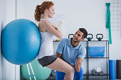 Smiling professional personal trainer helping sportswoman exercising with ball
