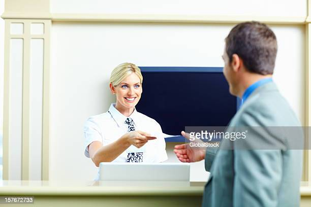 Smiling receptionist giving an airline ticket to business man