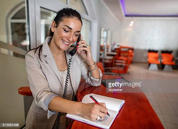 Smiling receptionist making appointment over the phone.
