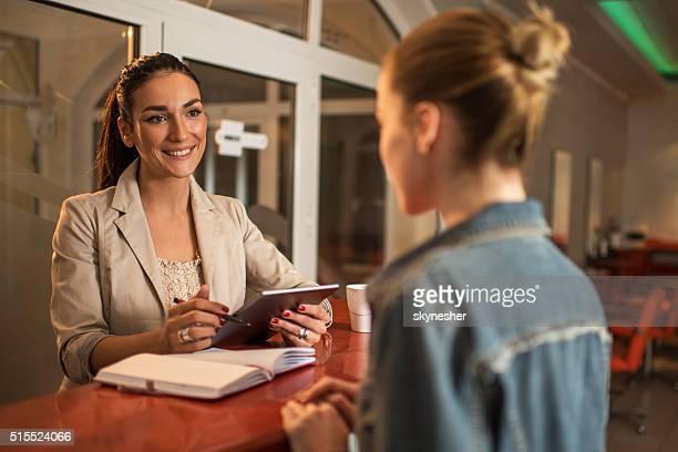 Souriant réceptionniste parler au client dans un salon de beauté.