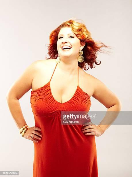 Femme souriante aux cheveux rouge portant robe rouge